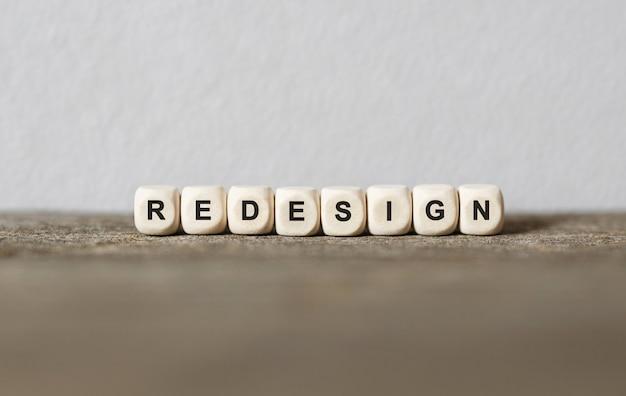Słowo redesign wykonane z drewnianych klocków,