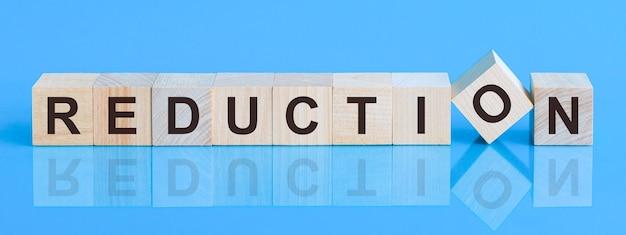 Słowo redukcji napisane na bloku drewna. słowo redukcji składa się z drewnianych klocków leżących na żółtym stole