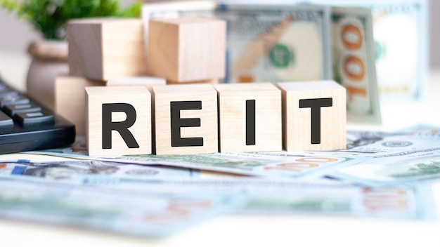 Słowo reit na kostkach drewna, banknotach i kalkulatorze. koncepcja biznesu, marketingu i handlu