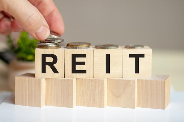 Słowo reit napisane na drewnianych kostkach. ręka mężczyzny umieszcza monety na powierzchni sześcianu. zielona roślina doniczkowa na tle. koncepcja biznesu i finansów. reit - fundusz powierniczy ds. inwestycji w nieruchomości