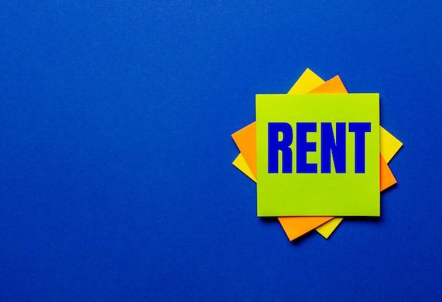 Słowo rent jest napisane na jasnych naklejkach na niebieskim stole