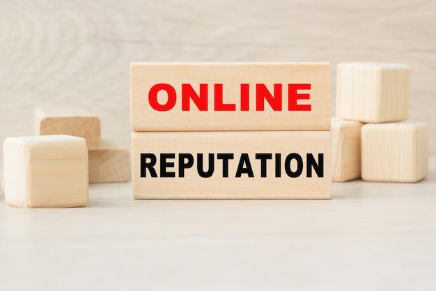 Słowo reputacja online jest napisane na drewnianej konstrukcji z kostek.