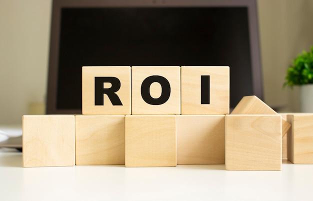 Słowo roi jest napisane na drewnianych kostkach leżących na biurowym stole przed laptopem. pomysł na biznes.