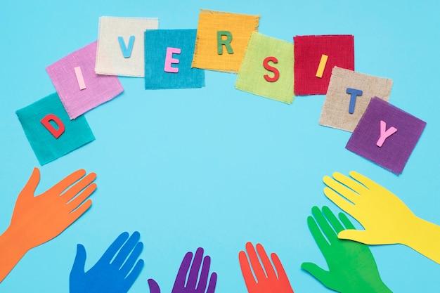 Słowo różnorodność wykonane z kolorowych kart obok kolorowych papierowych rąk