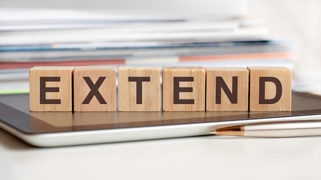 Słowo rozszerzać jest zapisane na drewnianych kostkach stojących na notatniku, na powierzchni stosu dokumentów
