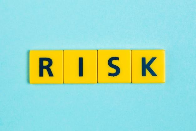 Słowo ryzyka na płytkach scrabble