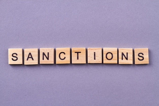 Słowo sankcji wykonane z drewnianych kostek. na białym tle na fioletowym tle.