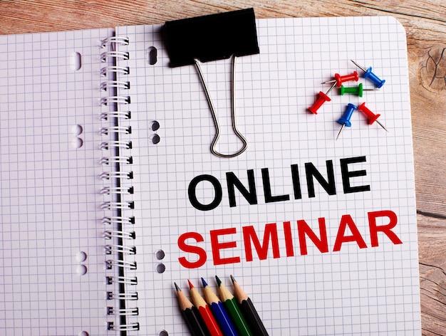 Słowo seminarium online zapisane jest w zeszycie obok wielokolorowych ołówków i guzików na drewnianym tle.