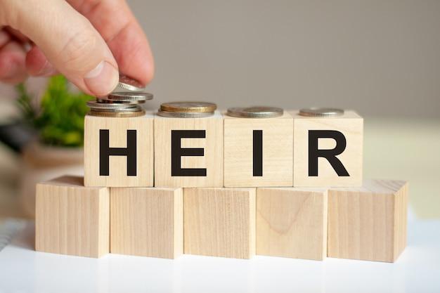 Słowo spadkobierca napisane na drewnianych kostkach. ręka mężczyzny umieszcza monety na powierzchni sześcianu. zielona roślina doniczkowa na tle. koncepcja biznesu i finansów.