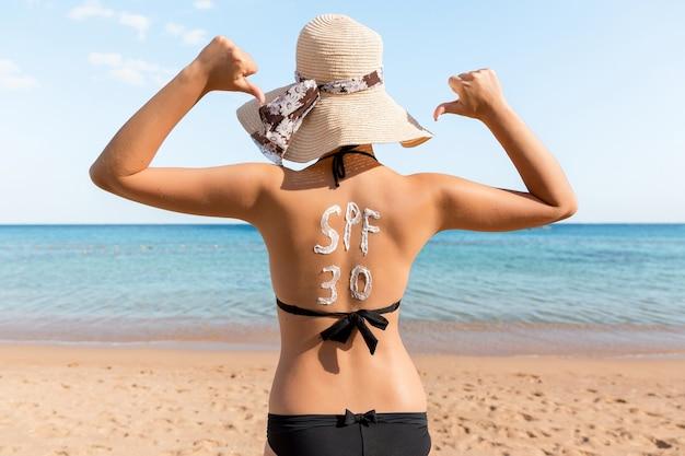Słowo spf 30 jest narysowane kremem z filtrem przeciwsłonecznym na plecach kobiety relaksującej się na plaży.