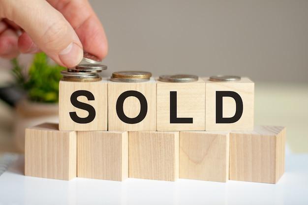 Słowo sprzedawane napisane na drewnianych kostkach. ręka mężczyzny umieszcza monety na powierzchni sześcianu. zielona roślina doniczkowa na tle. koncepcja biznesu i finansów.