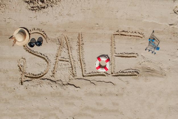 Słowo sprzedaż jest namalowane na piasku pojęcie lata, letnie kanikkuly, wakacje, święta