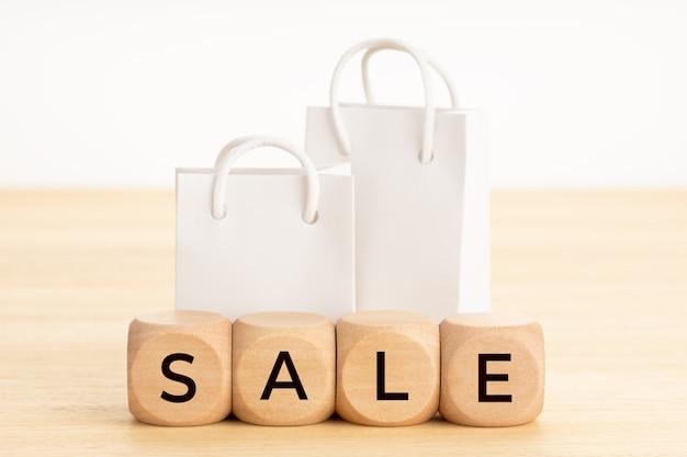Słowo sprzedaż na drewnianych klockach i puste papierowe torby na zakupy na stole
