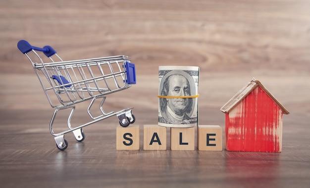 Słowo sprzedaż na drewnianych kostkach z modelem domu, koszykiem i pieniędzmi.