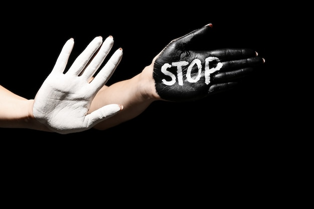 Słowo stop napisane na malowanej kobiecej dłoni na ciemnym tle. pojęcie rasizmu