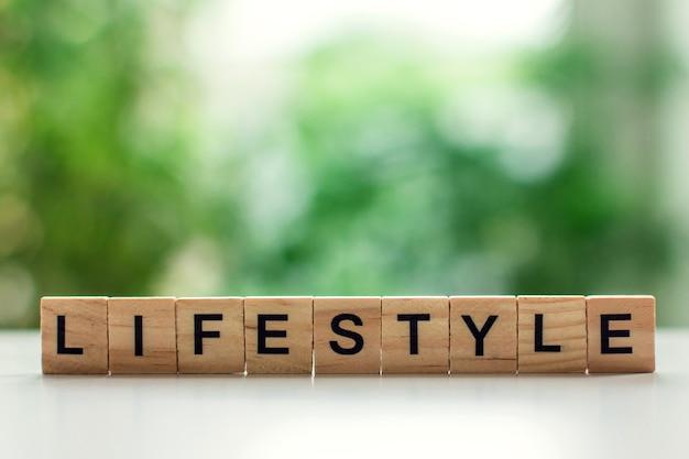 Słowo styl życia wiadomość znak drewnianych kostek na jasnym stole na tle zielonych liści w nieostrości