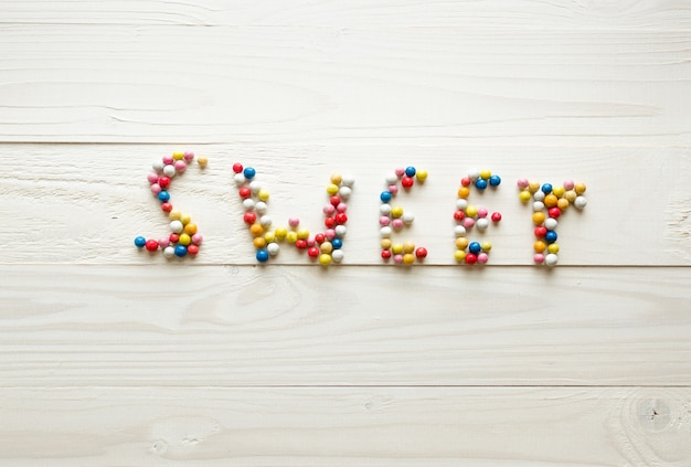 Słowo sweet wykonane z kolorowych okrągłych cukierków na białym drewnianym tle