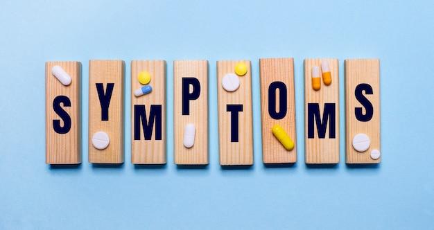 Słowo symptoms jest zapisane na drewnianych klockach na jasnoniebieskim stole obok tabletek