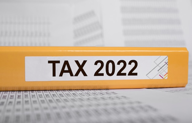Słowo systemu podatkowego na żółtym folderze na dokumentach