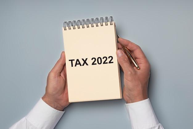 Słowo systemu podatkowego na żółtym papierze w rękach biznesmena