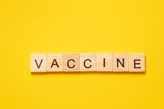 Słowo szczepionka wykonane z drewnianych liter na żółtym tle.