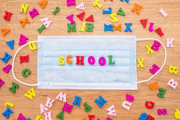 """Słowo """"szkoła"""" z kolorowych liter na masce. pojęcie kwarantanny i stylu życia podczas pandemii."""