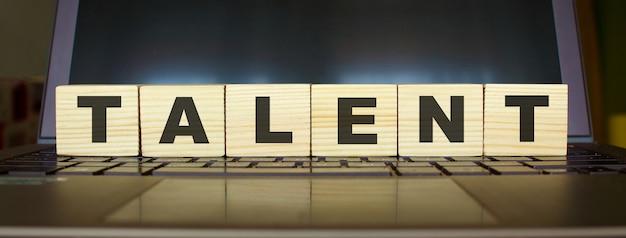 Słowo talent. drewniane kostki z literami na białym tle na klawiaturze laptopa