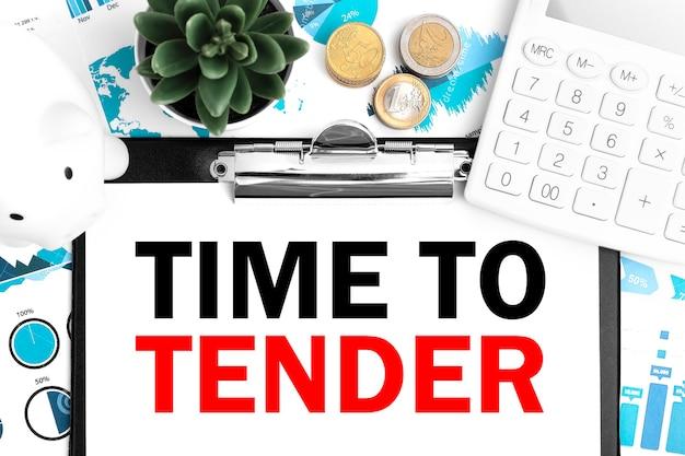 Słowo time to tender na schowku, śwince, kalkulatorze, monecie, wykresie, diagramie i długopisie na biurku. pomysł na biznes.
