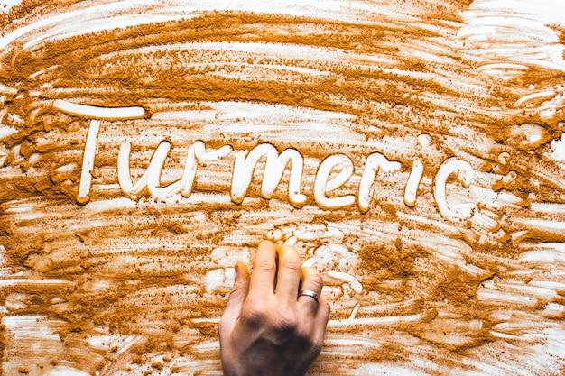 Słowo turmericon na białym tle przyprawa posypana