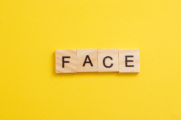 Słowo twarz wykonane z drewnianych liter na żółtym tle.