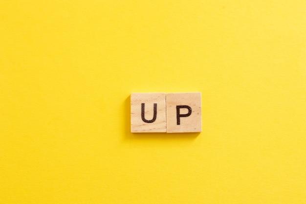 Słowo up wykonane z drewnianych liter na żółtym tle. pojęcie wzrostu