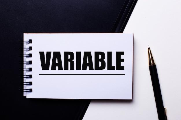 Słowo variable zapisane na czerwono na czarno-białej ścianie w pobliżu długopisu