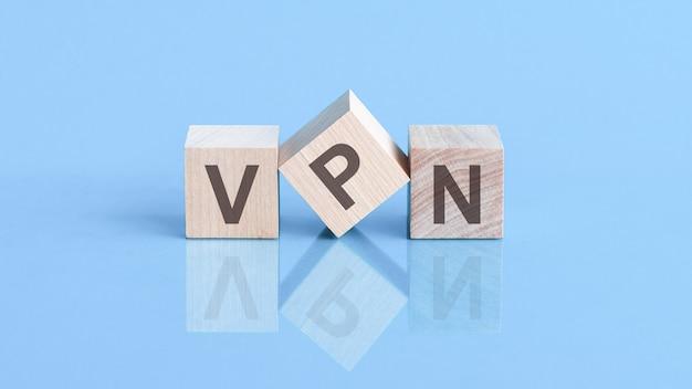 Słowo vpn składa się z drewnianych kostek leżących na niebieskim stole, koncepcja