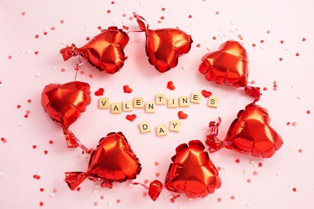 Słowo walentynki z bloków liter i czerwonych serc dookoła balonów foliowych.