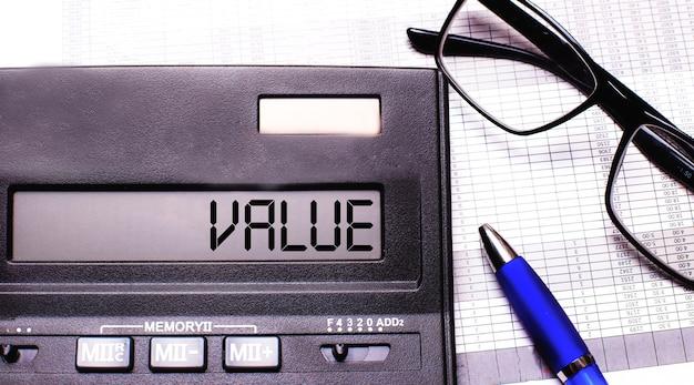 Słowo wartość jest zapisane w kalkulatorze obok okularów w czarnych oprawkach i niebieskiego długopisu