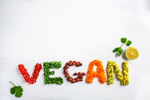 Słowo weganin na białym tle, odgórny widok. koncepcja wegańskiego jedzenia. wegański złożony z fasoli, guacamole, warzyw i ziół.