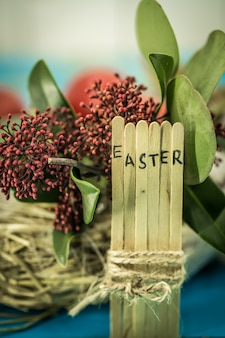 Słowo wielkanoc w koncepcyjnym tekście bloku na drewnianych patykach, piękne świąteczne jajka z zielenią