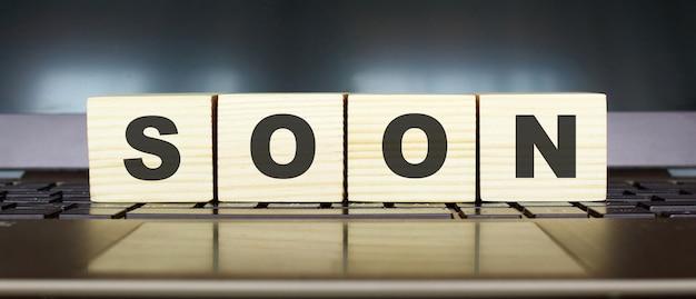 Słowo wkrótce. drewniane kostki z literami na białym tle na klawiaturze laptopa
