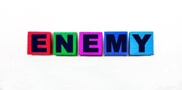 Słowo wrog jest napisane na kolorowych kostkach na jasnej powierzchni