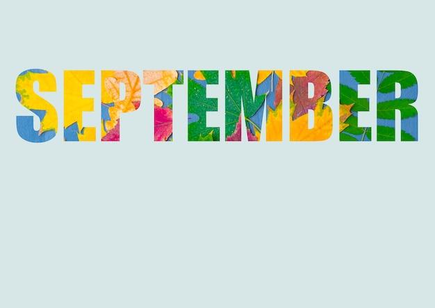 Słowo wrzesień składa się z jasnych, kolorowych jesiennych liści różnych roślin, wyizolowanych na pastelowym niebieskim tle. miesiąc jesienny wrzesień. jasny kalendarz jesienny