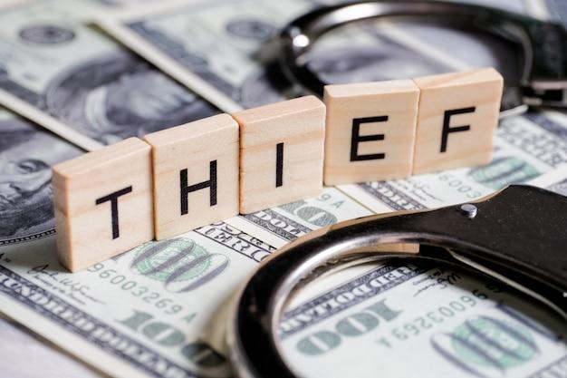 Słowo wykonane z drewnianych liter - złodziej, na szarym tle z nami dolarów obok lupy. oznaczenie przestępstwa.