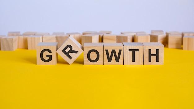 Słowo wzrostu napisane na bloku drewna. słowo redukcji jest wykonane z drewnianych klocków leżących na żółtym stole. pomysł na biznes