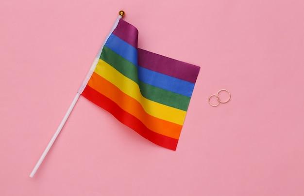 Ślub lgbt. lgbt tęczowa flaga i złote pierścienie na różowym tle. tolerancja, wolność