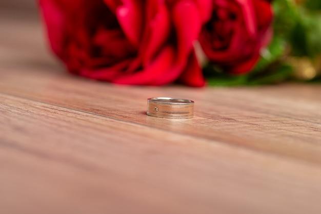 Ślub lub pierścionek zaręczynowy leżący na drewnianej powierzchni obok pięknych czerwonych róż