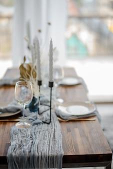 Ślub lub świąteczny nakrycie stołu. talerze, kieliszki do wina i sztućce z szarą i jasnoniebieską dekoracyjną tkaniną na drewnianym stole. piękna aranżacja.