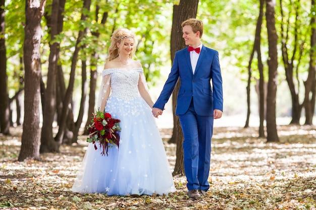 Ślub młodej pary z spacerkiem po zielonym parku.