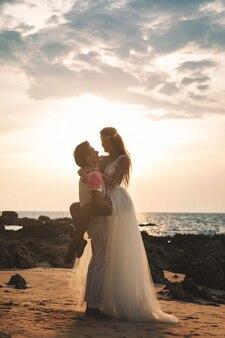 Ślub na plaży. młoda i piękna para małżeńska w objęciach.