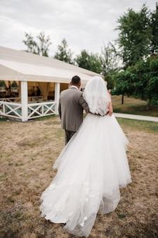 Ślub na wiosnę. panna młoda i pan młody idą na ceremonię za rękę. restauracja. biała sukienka. szary strój.