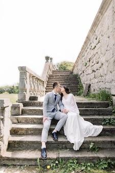 Ślub, pan młody azjatycki i panna młoda trzymając się za ręce, siedząc na starożytnych kamiennych schodach, obok starego zamku