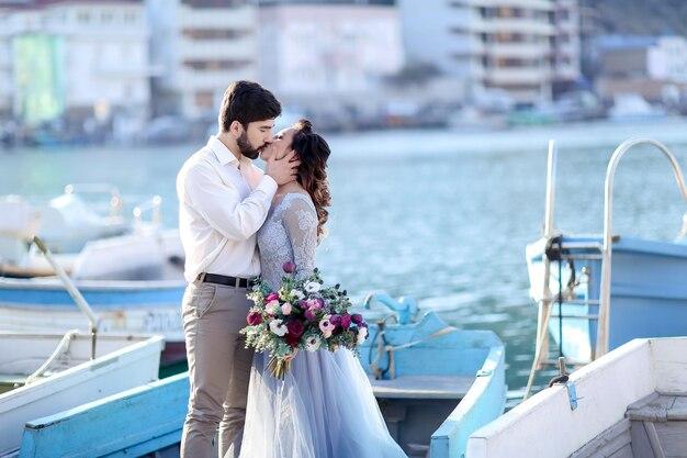 Ślub panny młodej i pana młodego na molo z łodziami na morzu